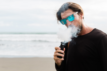 Man with beard and sunglasses smoking electronic sigarette outdoor on sunset beach. Young hipster male vaping on sea front.