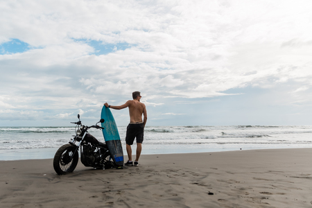 male person looking for inspiration while standing near sportive motorbike. holding surfboard in hands. Young man surfer enjoying recreation near to ocean. Stok Fotoğraf