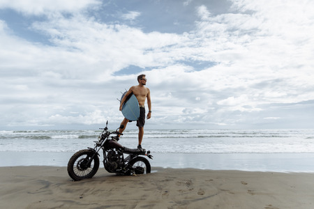 male person looking for inspiration while standing on sportive motorbike. holding surfboard in hands. Young man surfer enjoying recreation near to ocean.