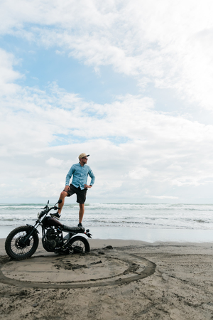 Man stands on a motorcycle. Ocean beach Bali. back wheel of a motorcycle in sand. male person looking for inspiration while standing on sportive motorbike. Young man surfer enjoying recreation near to ocean.