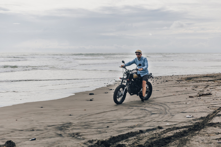 Man in cap riding motorcycle on beach. Moto cross dirtbiker on beach sunset on Bali. Young hipster male enjoying freedom and active lifestyle, having fun on a bikers tour. Banque d'images