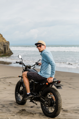 Man in cap riding motorcycle on beach. Moto cross dirtbiker on beach sunset on Bali. Young hipster male enjoying freedom and active lifestyle, having fun on a bikers tour. Stok Fotoğraf
