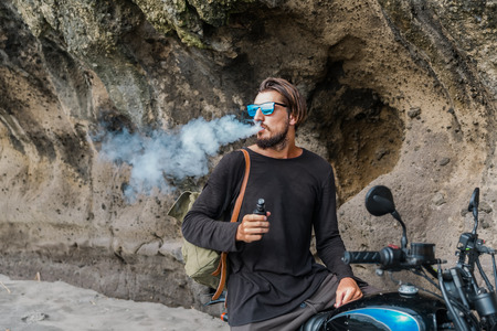 Man with beard and sunglasses seat on motorcycle smoking electronic sigarette outdoor on sunset beach. Young hipster male vaping on sea front. Stok Fotoğraf
