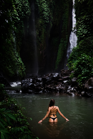 Back view of beautiful woman bathing and relaxing in natural swimming pool before waterfall in natural park on tropical island. beautiful waterfall in the Bali, Indinesia