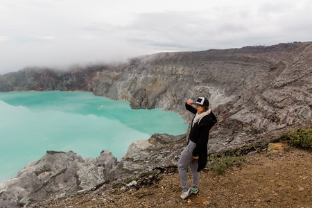 Woman tourist looks at the sulphur lake on the Ijen volcano on the island Java in Indonesia. Hiker female travel on top mountain, travel concept