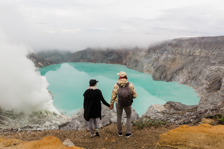 Couple tourists looks at the sulphur lake on the Ijen volcano on the island Java in Indonesia. Hikers travel on top mountain, travel concept Stok Fotoğraf