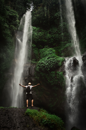 Man enjoying waterfall raised hands. Travel Lifestyle and success concept vacations into the wild nature on background mountain and rainforest.