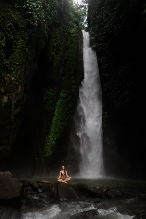 Beautiful young woman meditating in lotus position while doing yoga in a wonderful forest near waterfall. Beautiful female Practicing Yoga on Rock near Tropical Waterfall Stok Fotoğraf