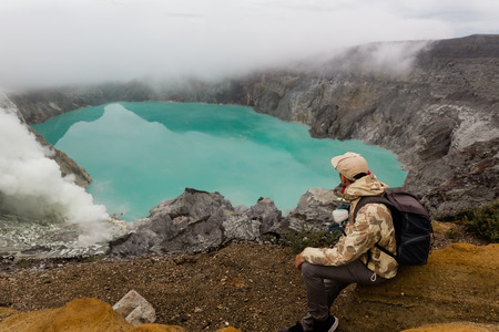 Man tourist looks at the sulphur lake on the Ijen volcano on the island Java in Indonesia. Hiker man with backpack travel on top mountain, travel concept Stok Fotoğraf