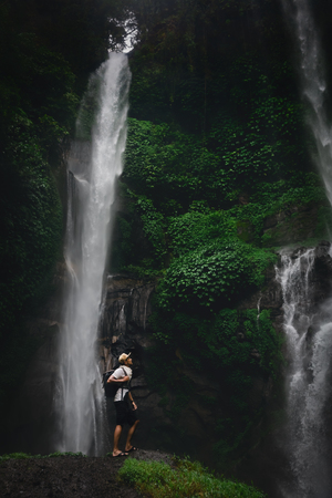 Happy man backpacker enjoying amazing tropical waterfall on background nature landscape. Travel Lifestyle and success concept vacations into the wild nature on background mountain and rainforest