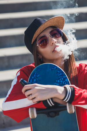 Vaping girl. Young woman with skateboard vape e-cig. Pretty young female in black hat, red clothing vape ecig, vaping device at the sunset. Toned image. Hip-hop style. Banque d'images
