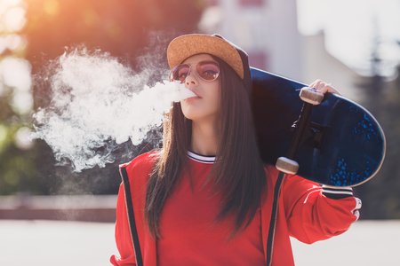 Vaping girl. Young woman with skateboard vape e-cig. Pretty young female in black hat, red clothing vape ecig, vaping device at the sunset. Toned image. Hip-hop style. Stok Fotoğraf - 123735388