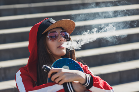 Vaping girl. Young woman with skateboard vape e-cig. Pretty young female in black hat, red clothing vape ecig, vaping device at the sunset. Toned image. Hip-hop style. Фото со стока