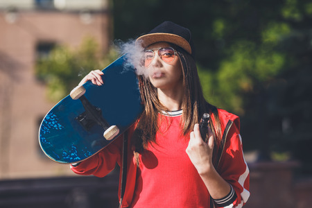 Vaping girl. Young woman with skateboard vape e-cig. Pretty young female in black hat, red clothing vape ecig, vaping device at the sunset. Toned image. Hip-hop style. Stok Fotoğraf - 123737014
