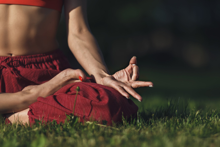 Young woman practicing yoga outdoors. Female meditate outdoor in the summer city park. Hands coseup, selective focus.
