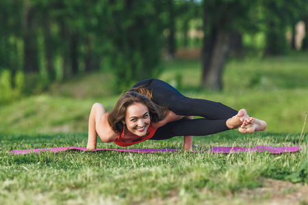 Young woman doing yoga exercises in the summer city park. Health lifestyle concept. Stok Fotoğraf - 123737020