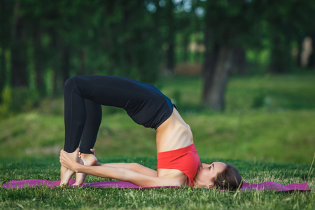 Young woman doing yoga exercises in the summer city park. Health lifestyle concept. Stok Fotoğraf - 123737022
