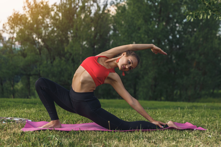 Young woman doing yoga exercises in the summer city park. Health lifestyle concept. Stok Fotoğraf - 123737532