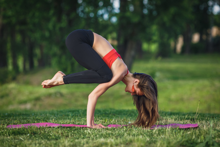 Young woman doing yoga exercises in the summer city park. Health lifestyle concept. Stok Fotoğraf - 123737538