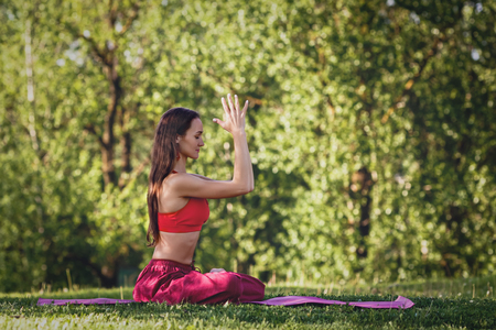 Young woman practicing yoga outdoors. Female meditate outdoor in the summer city park. Фото со стока