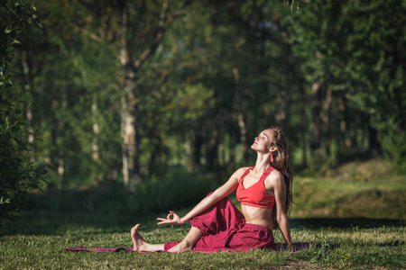 Young woman doing yoga exercises in the summer city park. Health lifestyle concept. Фото со стока