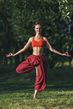 Young woman doing yoga exercises in the summer city park. Health lifestyle concept. Stok Fotoğraf - 123739527