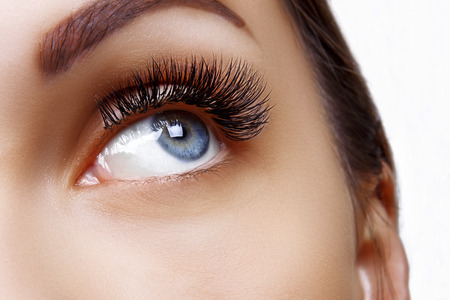 Eyelash Extension Procedure. Woman Eye with Long Blue Eyelashes. Ombre effect. Close up, selective focus.