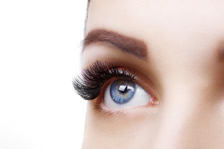 Wimpernverlängerungsverfahren. Frauenauge mit langen blauen Wimpern. Ombre-Effekt. Nahaufnahme, selektiver Fokus.