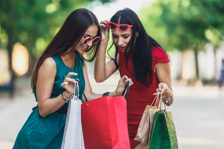 Beautiful happy females in sun glasses looking into shopping bags walking at the street. Positive emotions and Shopping day concept. Stok Fotoğraf - 124798375
