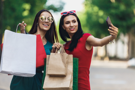 Beautiful happy girls in sun glasses holding shopping bags, making selfie on smart phone and smiling. Sale and consumerism concept. Stok Fotoğraf - 124798376