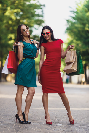 Young attractive girls with shopping bags in the summer city. Beautiful women in sunglasses looking at camera and smiling. Positive emotions and Shopping day concept. Stok Fotoğraf - 124798377