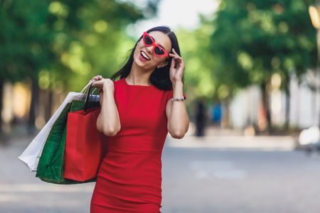 Portrait of young happy smiling woman with shopping bags enjoying in shopping. Positive emotions and Shopping day concept.