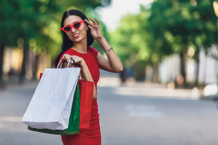 Portrait of young happy smiling woman with shopping bags enjoying in shopping. Positive emotions and Shopping day concept. Stok Fotoğraf - 124798403