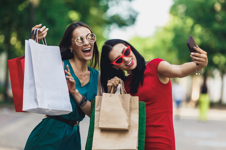 Beautiful happy girls in sun glasses holding shopping bags, making selfie on smart phone and smiling. Sale and consumerism concept. Фото со стока