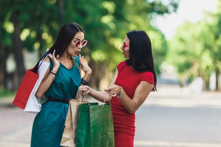 Beautiful happy females in sun glasses looking into shopping bags walking at the street. Positive emotions and Shopping day concept. Stok Fotoğraf - 124798407