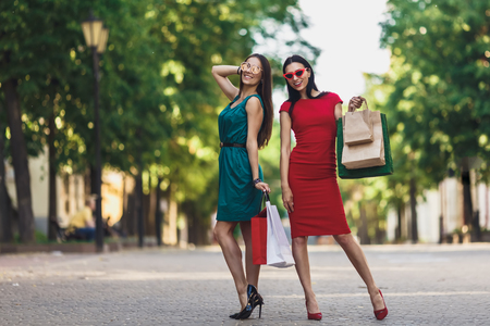 Young attractive girls with shopping bags in the summer city. Beautiful women in sunglasses looking at camera and smiling. Positive emotions and Shopping day concept. Фото со стока