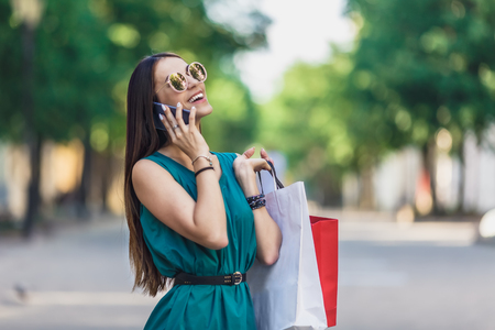 Close up of young charming dark-haired caucasian female with shopping bags smiling with teeth and talking on phone. Positive emotions and Shopping day concept.