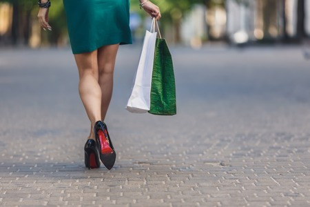 Close-up of young woman carrying shopping bags while walking along the street. Woman sexy legs with handbag. Positive emotions and Shopping day concept. Stok Fotoğraf - 124798409