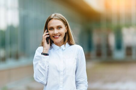 Young famale calling on a smartphone. Attractive businesswoman talking by phone. Office building Background. Technology internet and happy people concept.