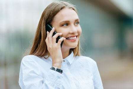 Młoda famale dzwoniąc na smartfonie. Atrakcyjny bizneswoman opowiada telefonem. Budynek biurowy tło. Technologia internet i koncepcja szczęśliwych ludzi.