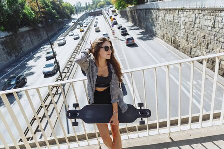 Beautiful young woman with longboard on the bridge in the city in sunny weather. Young hipster girl posing with longboard, skateboard, street photo, life style, freedom, happy face.
