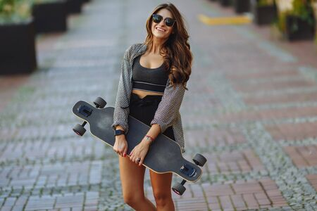 Beautiful young woman with longboard on the city street in sunny weather. Young hipster girl posing with longboard, skateboard, streetphoto, life style, freedom, happy face.