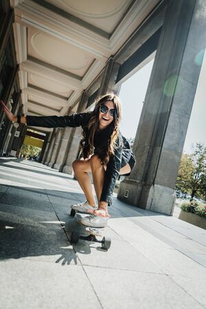 Beautiful young skater woman riding on her longboard in the city. Stylish girl in street clothes rides on a longboard. Skateboard, street photo, life style, freedom, happy face concept.