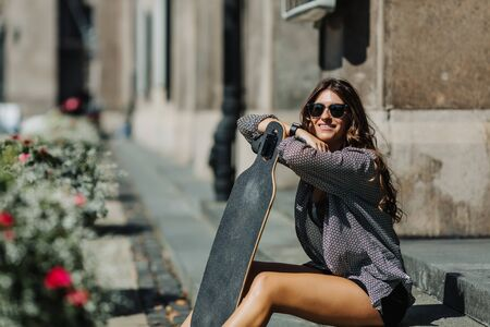 Portrait of Beautiful young woman sitting on the ground and holding a longboard in the city street sunny weather. Young hipster girl posing with skateboard.