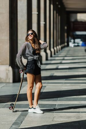 Beautiful young woman with longboard on the city street in sunny weather. Young hipster girl posing with skateboard. Фото со стока