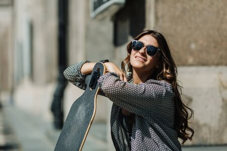 Close up Portrait of Beautiful young woman sitting on the ground and holding a longboard in the city street sunny weather. Young hipster girl posing with skateboard. Фото со стока