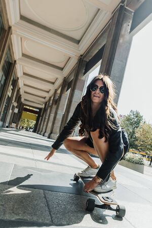 Beautiful young skater woman riding on her longboard in the city. Stylish girl in street clothes rides on a longboard.