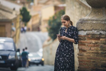Pretty young woman in a black dress using smartphone at old town street. Travel by Europe. Stock Photo