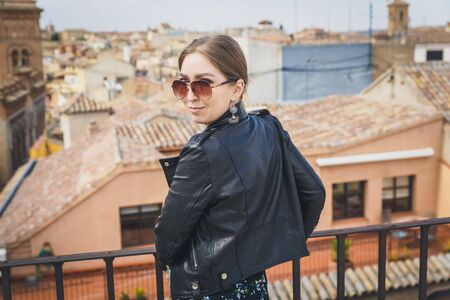 Stylish woman posing in the old part of the town against tile roofs. Medieval city of Toledo in the center of Spain.