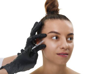 Closeup Beautician Hands Doing Facial Skin Lifting Injection To female. Beautiful young woman face and hand in glove with syringe making injection.